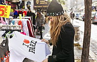 France, Paris, female tourist at a souvenir stand - MGO03125