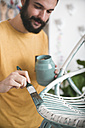 Bearded man painting wicker armchair at home - RTBF00770
