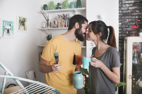 Young couple kissing between paintbrushes and tea mugs - RTBF00773