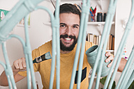 Portrait of smiling man painting wicker armchair at home - RTBF00779