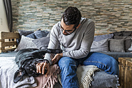 Man playing with his dog on the couch at home - TCF05321