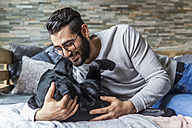 Smiling man cuddling with his dog on the couch at home - TCF05324