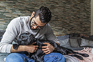 Man cuddling with his dog on the couch at home - TCF05327