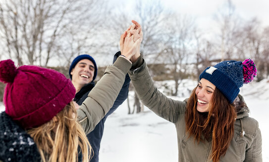 Three friends joining their hands in the snow - MGOF03150