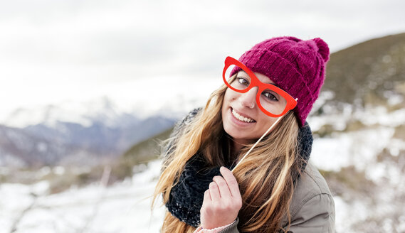 Young woman with fake glasses having fun in the snowy mountains - MGOF03153