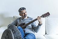 Mature man at home playing electric guitar - TCF05332