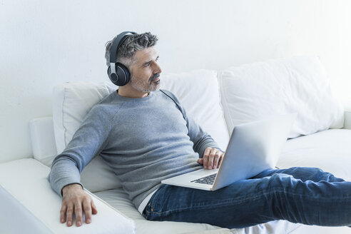 Mature man at home using laptop and wearing headphones - TCF05338