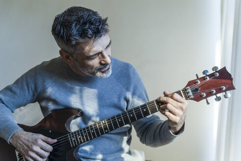 Mature man at home playing electric guitar - TCF05350