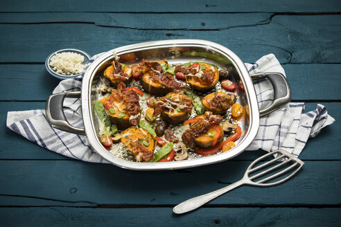 Vegetables, herbs and fried bacon gratinated with cheese in a pan - MAEF12184