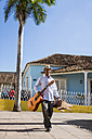 Cuba, walking man with guitar and stool on the street - MAUF01030