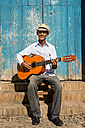 Cuba, portrait of man playing guitar on the street - MAUF01033