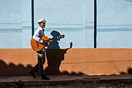 Cuba, man with guitar walking on the street - MAUF01036
