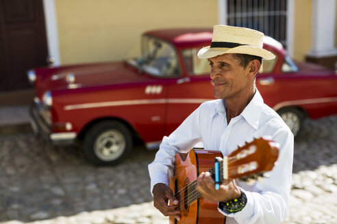 Cuba, Trinidad, man playing guitar on the street - MAUF01039
