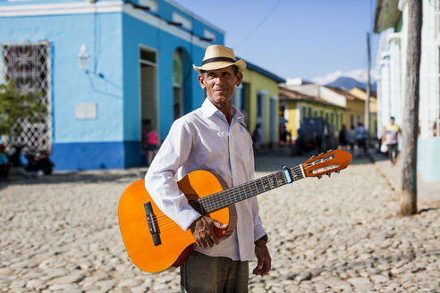 Cuba, Trinidad, man with guitar standing on the street - MAUF01042