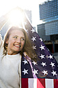 Spain, Barcelona, portrait of smiling young woman with US American flag - KKAF00550