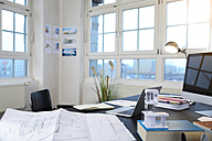 Desk with construction plan in a modern informal office - FKF02194