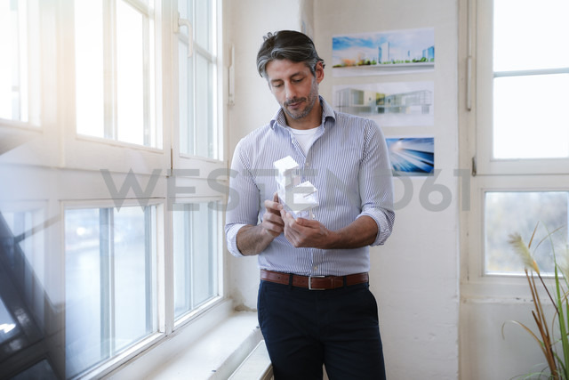 Man in office looking at architectural model - FKF02197