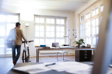 Man with bicycle in a modern informal office - FKF02203