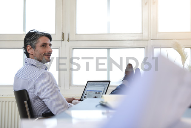 Man using laptop at the window in office - FKF02209