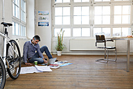 Man using laptop on the floor in a modern informal office - FKF02212