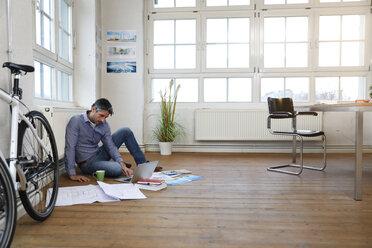 Man using laptop on the floor in a modern informal office - FKF02212