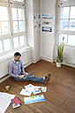 Man using laptop on the floor in office - FKF02215