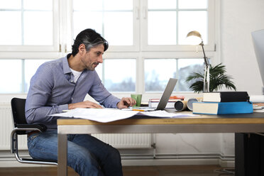 Man using laptop at desk in office - FKF02218