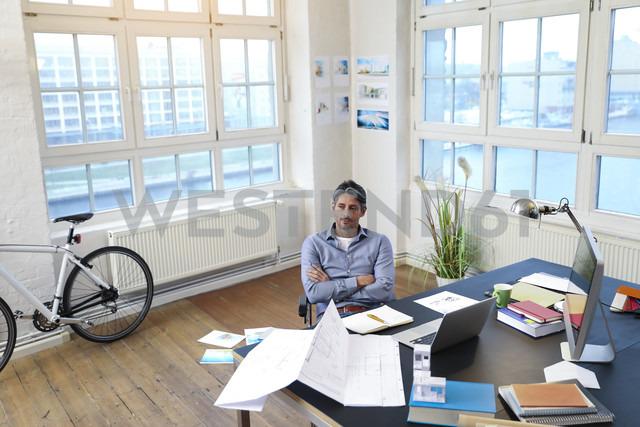 Man at desk in office thinking - FKF02221