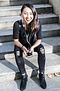 Portrait of young woman dressed in black sitting on steps listening music with earphones and cell phone - GIOF02497
