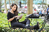 USA, New York, young woman sitting at city park using tablet - GIOF02500