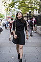 USA, New York City, Manhattan, fashionable young woman dressed in black walking on pavement - GIOF02503