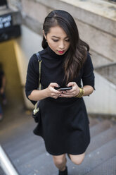 USA, New York City, Manhattan, young woman dressed in black walking upstairs text messaging - GIOF02506