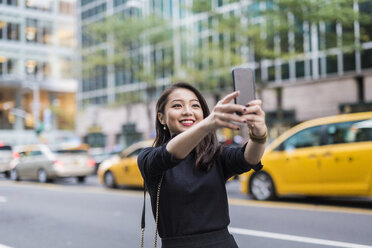 USA, New York City, Manhattan, portrait of smiling young woman taking selfie with smartphone - GIOF02509