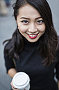 Portrait of smiling young woman with coffee to go - GIOF02512