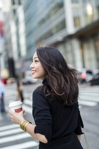 USA, New York City, Manhattan, smiling young woman with coffee to go crossing the street - GIOF02515