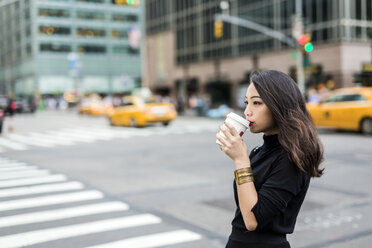 USA, New York City, Manhattan,  young woman drinking coffee to go on  the street - GIOF02518