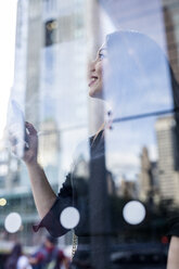 USA, New York City, Manhattan, smiling young woman behind glass pane watching something - GIOF02527