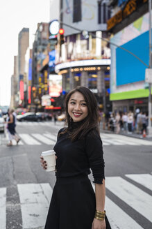 USA, New York City, Manhattan,  happy young woman with coffee to go on the street - GIOF02530