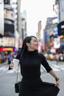 USA, New York City, Manhattan,  young woman dressed in black with coffee to go on the street - GIOF02533