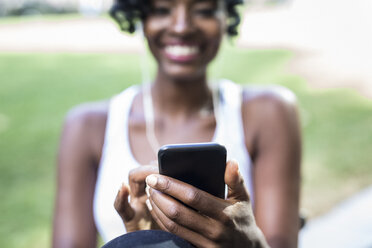Woman using cell phone in a park, close-up - GIOF02539