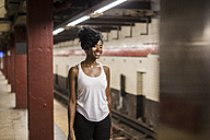 USA, New York City, Manhattan, smiling woman waiting at subway station platform - GIOF02545