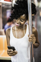 USA, New York City, Manhattan, portrait of happy woman looking at cell phone in underground train - GIOF02551