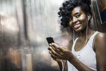 Portrait of happy woman with cell phone and earphones in underground train - GIOF02554