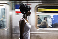USA, New York City, Manhattan, woman with earphones on subway station platform - GIOF02557