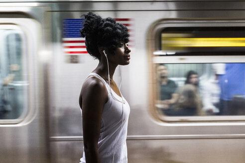 USA, New York City, Manhattan, woman with earphones on subway station platform - GIOF02557