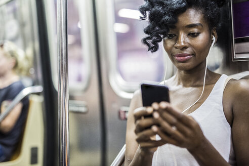 Portrait of woman looking at cell phone in underground train - GIOF02560