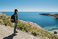 Bolivia, Titicaca lake, Isla del sol, woman with backpack enjoying the view - GEMF01546