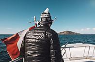 Peru, Titicaca lake, Taquile, man on a boat with Peruvian flag - GEMF01549