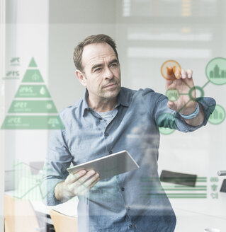 Businessman with tablet touching glass pane with data in office - UUF10242