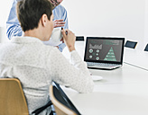 Businessman and businesswoman discussing data on laptop - UUF10245